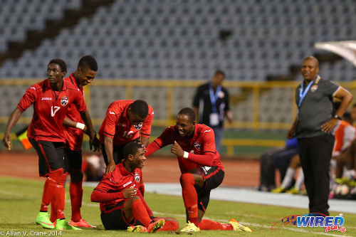 Photo: Trinidad and Tobago under-20 midfielder Aikim Andrews (seated) celebrates his goal against Curaçao with his teammates. (Courtesy Allan V Crane/Wired868)