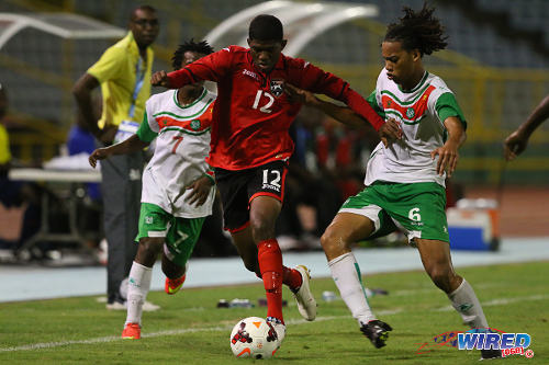 Photo: Trinidad and Tobago midfielder Kishun Seecharan (centre) holds off Suriname player Ervin Slagveer during the 2014 Under-20 Caribbean Cup. (Courtesy Allan V Crane/Wired868)