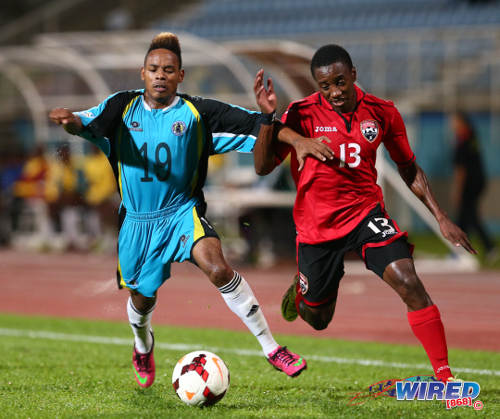 Photo: Trinidad and Tobago winger Cordell Cato (right) motors past St Lucia right back Erick Gabriel during the 2014 Caribbean Cup qualifying series. (Courtesy Allan V Crane/Wired868)