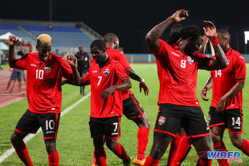 Photo: Trinidad and Tobago scorer Kevin Molino (far left) leads teammates Hughtun Hector (second from left) and captain Kenwyne Jones (second from right) in a goal dance during 2014 Caribbean Cup qualifying action against Antigua and Barbuda. (Courtesy Allan V Crane/Wired868)