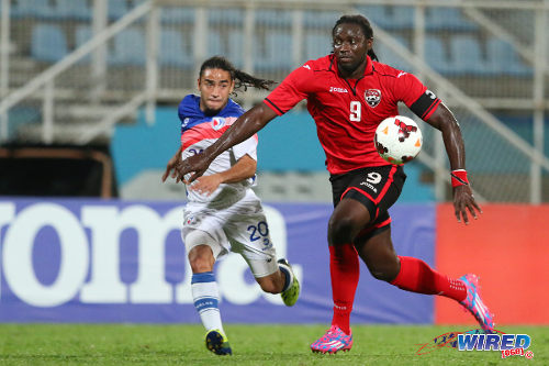 Photo: Trinidad and Tobago forward and captain Kenwyne Jones (right) drives past Dominican Republic left back Edward Acevedo during the 2014 Caribbean Cup qualifying series in Couva. (Courtesy Allan V Crane/Wired868)