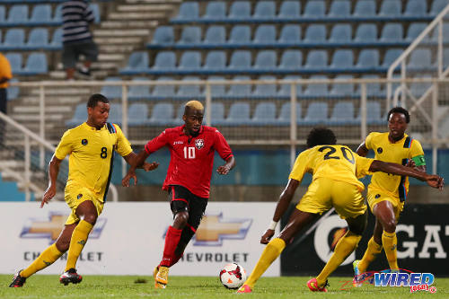 Photo: Trinidad and Tobago midfielder Kevin Molino (second from left) runs at Antigua and Barbuda players (from left) Keiran Murtagh, Akeem Thomas and Quinton Griffith during 2014 Caribbean Cup qualifying action. (Courtesy Allan V Crane/Wired868)