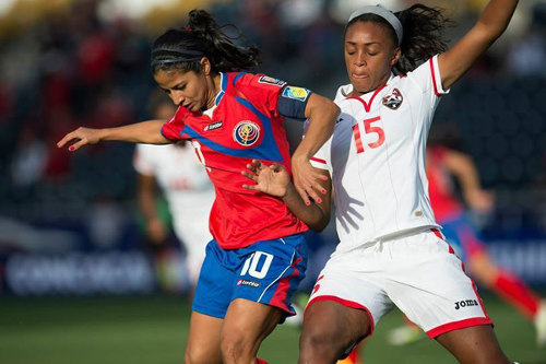 Photo: Trinidad and Tobago defender Liana Hinds (right) tries to stay close to Costa Rica playmaker Shirley Cruz during the 2014 CONCACAF Championships semifinal. (Courtesy CONCACAF)