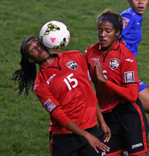 Photo: Trinidad and Tobago defender Lianna Hinds (left) keeps an eye on the ball against Haiti while teammate Brianna Ryce looks on during the 2014 CONCACAF Championship. (Courtesy CONCACAF)