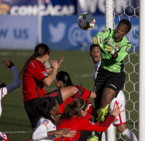 Photo: Trinidad and Tobago goalkeeper Kimika Forbes (right) punches clear of a crowded penalty area during the 2014 CONCACAF Championships third place play off against Mexico. (Copyright AFP 2014/Mitchell Leff)