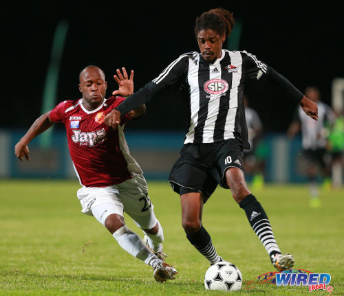 Photo: North East Stars utility player Kennedy Hinkson (left) pressures Central FC sweeper Marvin Oliver during the 2014 First Citizens Cup final in Couva. (Courtesy Allan V Crane/Wired868)