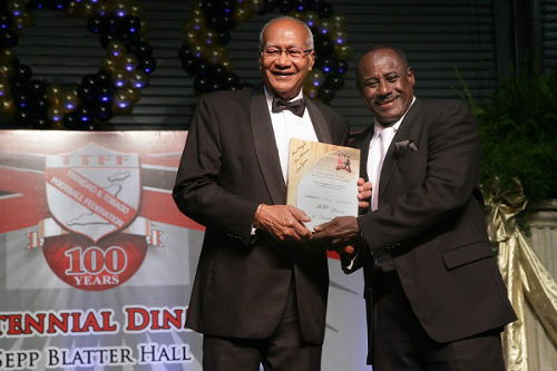 "Photo: Former Trinidad and Tobago stand-out player and coach Everald ""Gally"" Cummings (right) is recognised by former President Maxwell Richards at the TTFF's Centennial function."