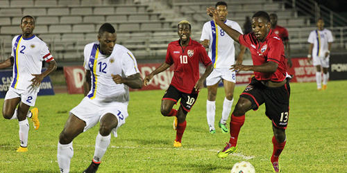 Photo: Trinidad and Tobago winger Cordell Cato (right) takes on the Curacao defence in the 2014 Caribbean Cup while teammate Kevin Molino looks on. (Courtesy CONCACAF)