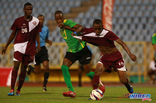 Photo: St Benedict's College midfielder Kadeem Gittens (centre) grabs hold of Mucurapo East Secondary player Kazim Donald (right) while Glenroy Pierre looks on in the 2014 National Intercol final. Mucurapo won 1-0 at the Hasely Crawford Stadium. (Courtesy Allan V Crane/Wired868)