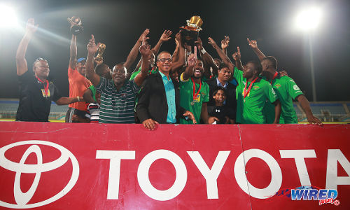 Photo: San Juan Jabloteh players celebrate capturing the 2014 Toyota Classic title with Pro League CEO Dexter Skeene (centre) and Toyota marketing manager Sean Shaffie (third from right). (Courtesy Allan V Crane/Wired868)