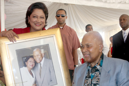 Photo: Prime Minister Kamla Persad-Bissessar (left) presents a framed photograph to her former Cabinet colleague and late Prime Minister ANR Robinson. (Courtesy Gov.tt)