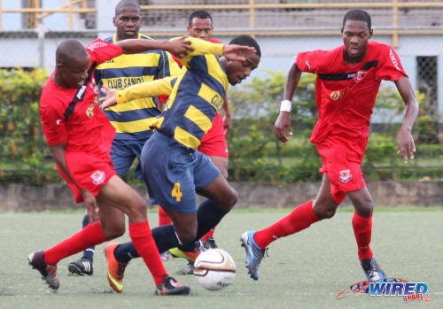 Photo: Club Sando midfielder Anthony Parris (centre) weaves through a group of Joe Public players during the 2013/14 Bmobile Super League competition. (Courtesy Wired868)