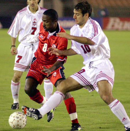 Photo: Trinidad and Tobago attacker Angus Eve (left) takes on a Canada player during the 2000 CONCACAF Gold Cup semi-finals. (Copyright AFP 2015)