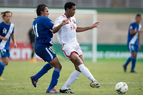 Photo: Trinidad and Tobago defender Brendon Creed (right) plays the ball away from Guatemala attacker Mario Hernandez. (Courtesy CONCACAF)