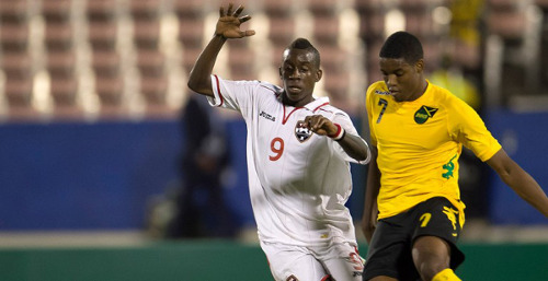 Photo: Trinidad and Tobago striker Kadeem Corbin (left) hustles Jamaica defender Malcolm Stewart during their CONCACAF Under-20 group opener. (Courtesy CONCACAF)