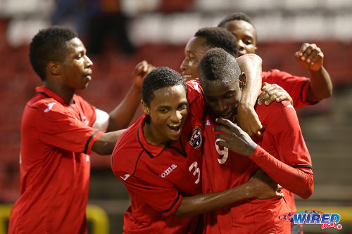 Photo: Trinidad and Tobago defender Martieon Watson (second from left) hugs striker Kadeem Corbin (right) during the 2014 Under-20 Caribbean Cup. (Courtesy Allan V Crane/Wired868)