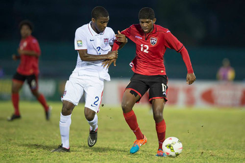Photo: Trinidad and Tobago winger Kishun Seecharan (right) is kept in grip by United States right back Shaquell Moore. Moore is the child of Trinidad and Tobago immigrants to the United States. (Courtesy CONCACAF)