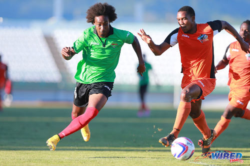 Photo: San Juan Jabloteh attacker Tyrone Charles (left) takes on Club Sando defender Andre Phillip during 2015 TTFA FA Trophy quarterfinal action in Malabar. (Courtesy Allan V Crane/Wired868)