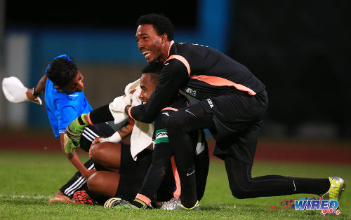 Photo: North East Stars hero Cleon John (centre) is congratulated by reserve goalie Stefan Berkeley after the 2015 TTFA FA Trophy final. (Courtesy Allan V Crane/Wired868)