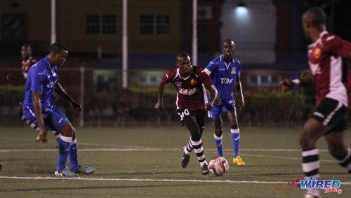 Photo: North East Stars attacker Keron Cummings (centre) in action during the 2015 TTFA FA Trophy quarterfinals while Defence Force captain Jerwyn Balthazar (second from right) looks on. (Courtesy Sinead Peters/Wired868)