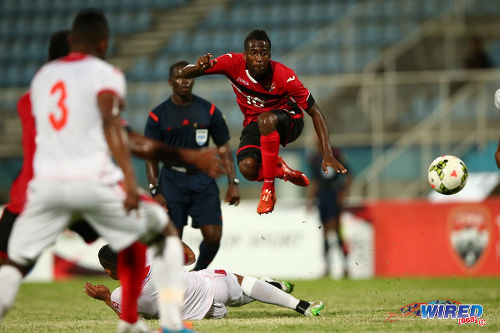 Photo: Trinidad and Tobago playmaker Kevin Molino (right) hurdles a tackle against Panama last night. (Courtesy Allan V Crane/Wired868)