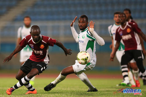 """Photo: North East Stars striker Gorean """"Ratty"""" Highley (left) takes on W Connection defender Christian Ocoro Viveros in the 2015 TTFA FA Trophy final. (Courtesy Allan V Crane/Wired868)"""