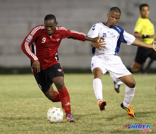 Photo: Trinidad and Tobago striker Devorn Jorsling (left) brushes aside a Martinique player during the 2012 Caribbean Cup semifinals. (Courtesy Allan V Crane/Wired868)