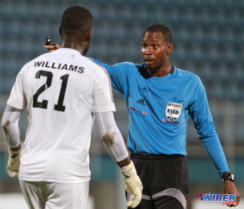 Photo: Referee Rodphin Harris (right) makes his point to Central FC goalkeeper Jan-Michael Williams during the 2013 First Cup semifinal. Central won 5-3 on penalties against W Connection. (Courtesy Allan V Crane/Wired868)