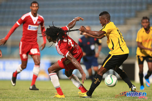 Photo: Don Bosco FC left back Jimmy Sara (right) hauls Central FC attacker Jason Marcano back by his locks during a physical Caribbean Club Championship semifinal contest. (Courtesy Allan V Crane/Wired868)