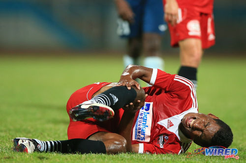 Photo: Central FC star Willis Plaza yells in pain after taking a blow to his knee against Police FC in the Pro Bowl semifinal. Plaza was replaced at halftime. (Courtesy Allan V Crane/Wired868)