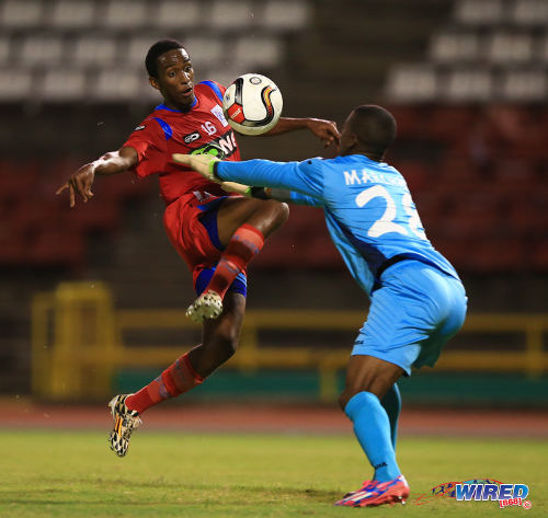 Photo: St Ann's Rangers player David Williams (left) flicks the ball past Defence Force goalkeeper Andre Marchan during Pro League action. (Courtesy Allan V Crane/Wired868)