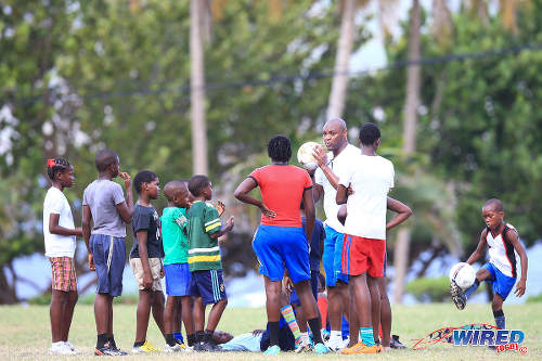 Photo: Former Chelsea striker Marcus Gayle (centre) is surrounded by young players in Speyside during the British Airways Tobago Legends Football Challenge community outreach programme. (Courtesy Allan V Crane/Wired868)