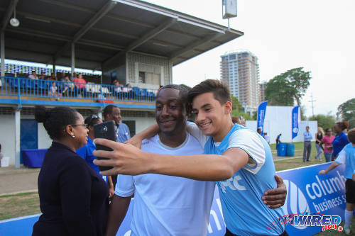 "Photo: Former Trinidad and Tobago and FC Porto star Russell ""Little Magician"" Latapy (centre) poses with a fan during the British Airways Tobago Legends Football Challenge community outreach programme at the St Mary's College ground in Serpentine Road, St Clair. (Courtesy Sinead Peters/Wired868)"
