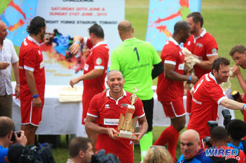 Photo: Liverpool striker Stan Collymore puts on an angelic smile as he lifts the Legends Football Challenge trophy. But they waged a bloody war to get it. (Courtesy Allan V Crane/Wired868)