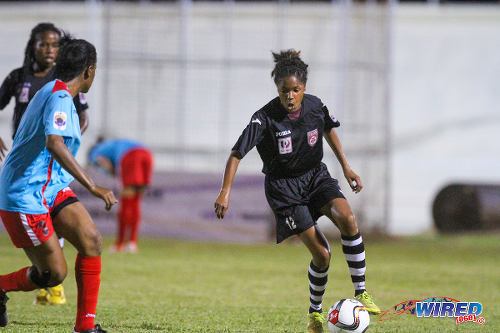 Photo: Petrotrin Oilers striker Kayla Taylor (right) runs at Wave defender Teneisha Cobham during 2015 WPL action in Palo Seco. (Courtesy Sinead Peters/Wired868)