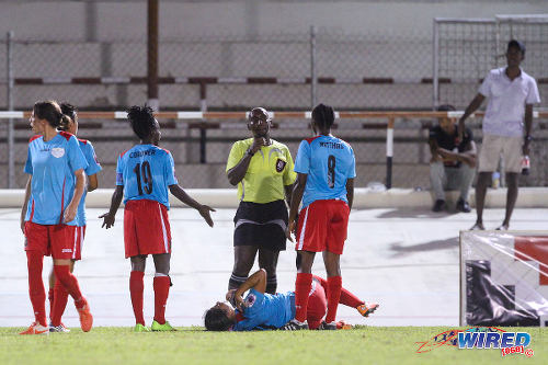 Photo: You didn't see that ref?! Wave players Kennya Cordner (centre) and Afiya Matthias (right) make a point to refere Keilon Bacchus while teammate Laura waits for treatment against Petrotrin Oilers. (Courtesy Sinead Peters/Wired868)