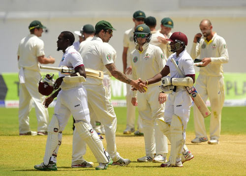 Photo: Australia pacer Mitchell Johnson (centre) offers a handshake to West Indies player Veerasammy Permaul at the end of the second Test. (Copyright Robyn Beck/AFP 2015)