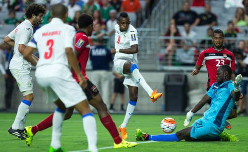 Photo: Trinidad and Tobago goalkeeper Jan-Michael Williams (right) reacts to block a shot from Cuba striker Maikel Reyes in the 2015 CONCACAF Gold Cup action. Williams was injured in the sequence. (Courtesy CONCACAF)