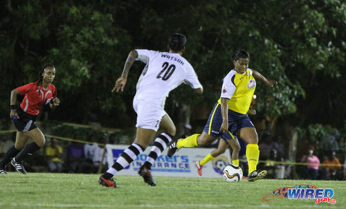Photo: Fuego attacker Shanelle Warrick (right) prepares to cross while Angels midfielder Tamar Watson (centre) and referee Crystal Sobers try to keep up with the action. (Courtesy Sinead Peters/Wired868)