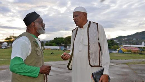 Photo: Jamaat-al-Muslimeen Imam Yasin Abu Bakr (right) chats with a colleague.