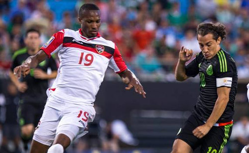 Photo: Trinidad and Tobago midfielder Kevan George (left) keeps an eye on Mexico captain Andres Guardado in 2015 CONCACAF Gold Cup action. (Courtesy CONCACAF)