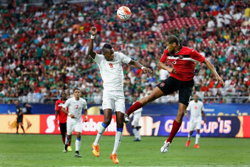 Photo: Trinidad and Tobago defender Radanfah Abu Bakr (right) wins a header against Cuba forward Maikel Reyes during the 2015 CONCACAF Gold Cup. (Courtesy CONCACAF)