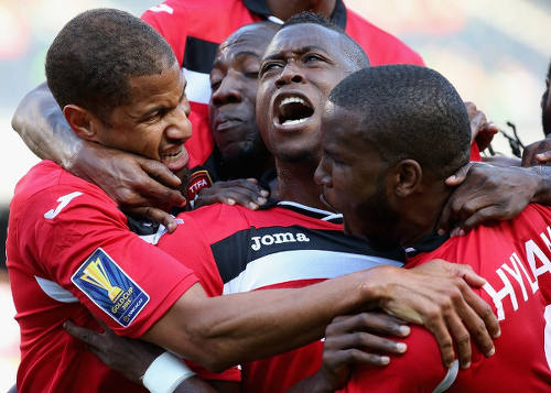 Photo: Trinidad and Tobago defender Sheldon Bateau (centre) celebrates the opening goal against Guatemala with teammates Radanfah Abu Bakr (left) and Khaleem Hyland during their 3-1 Gold Cup win. (Copyright Jonathan Daniel/AFP 2015)