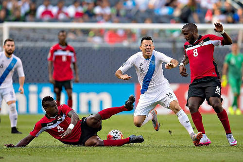 Photo: Trinidad and Tobago defender Sheldon Bateau (left) tackles Guatemala attacker Marco Papa in 2015 Gold Cup action. Looking on is teammate Khaleem Hyland (right). (Courtesy CONCACAF)