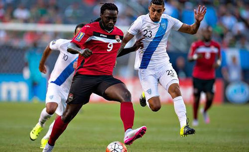 Photo: Trinidad and Tobago captain Kenwyne Jones (left) holds off Guatemala midfielder Jorge Aparicio in 2015 Gold Cup action. (Courtesy CONCACAF)