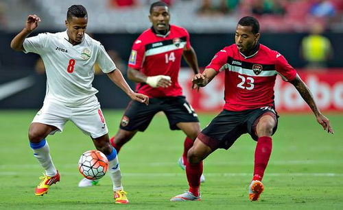 Photo: Trinidad and Tobago players Lester Peltier (right) and Andre Boucaud (centre) try to close down Cuba midfielder Alberto Gomez during their 2015 CONCACAF Gold Cup clash. (Courtesy CONCACAF)