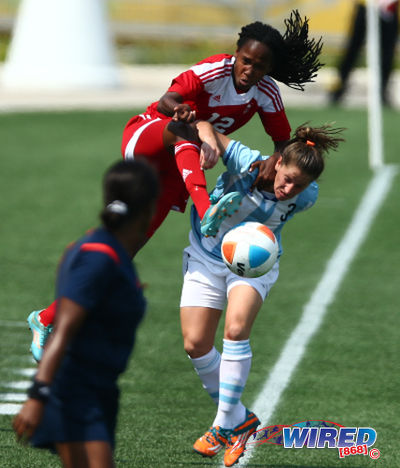 Photo: Trinidad and Tobago winger Ahkeela Mollon (left) climbs over Argentina defender Nerina Garcia during their 2-2 Toronto 2015 Pan American Games tie. (Courtesy Allan V Crane/Wired868)