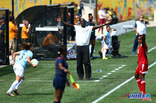 Photo: Former Trinidad and Tobago National Senior Women's Team coach Ross Russell (centre) and attacker Ahkeela Mollon (right) debate a refereeing decision while Argentina defender Nerina Garcia prepares to take a throw. Both teams played to a 2-2 draw in the Toronto 2015 Pan American Games. (Courtesy Allan V Crane/Wired868)