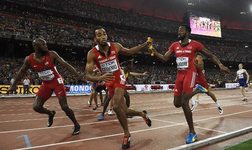 """Photo: Trinidad and Tobago's Machel Cedenio (centre) takes the baton from Deon Lendore in the final leg of the men's 4x400 metres final at the 2015 IAAF World Championships at the """"Bird's Nest"""" National Stadium in Beijing on 30 August 30 2015. USA's LaShawn Merritt (left) also receives the baton from Bryshon Nellum. (Copyright AFP 2015/ Franck Fife)"""