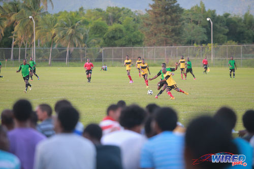 Photo: Prisons FC striker Curtis Carrington (centre) drives the ball past Cunupia defender Dale Simon for a late equaliser in their opening game of the season at the Youth Training Facility, Arouca. Looking on are YTC inmates. (Courtesy Allan V Crane/Wired868)